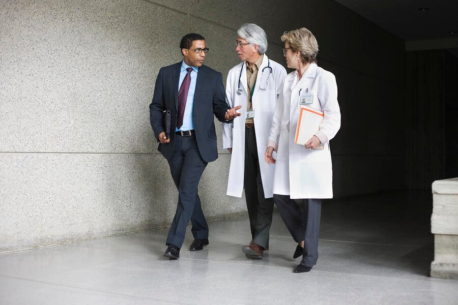 Two doctors in doctor jackets and a man in a business suit walking down a hallway together